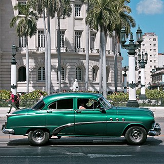 A green classic car in front of a white building