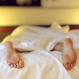 a person's feet sticking out from white sheets at the bottom of a bed