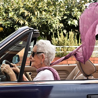 an elderly woman wearing sunglasses and a pink scarf driving a dark blue convertible
