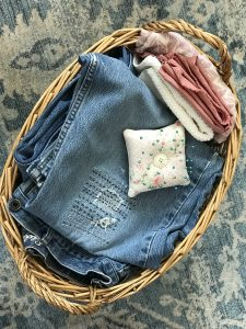 A wicker basket with mended jeans and other folded clothes and a square pin cushion on top, against a blue and white carpet.