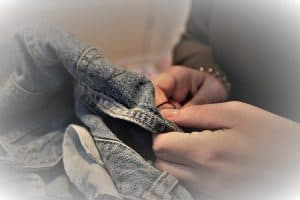 a person in a dark top mends a piece of denim clothing with needle and thread