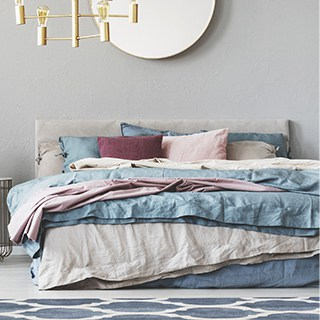 A made bed with pink, burgundy, blue, and white bedding.