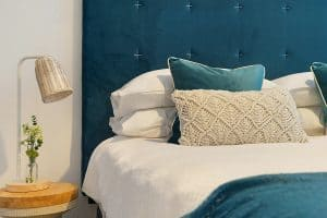 a small lamp on a small table next to a teal, white, and cream bed.