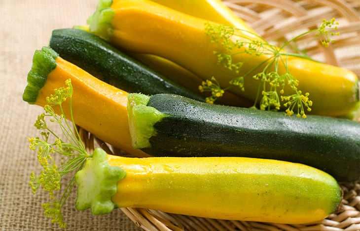 whole green and yellow summer squash in a wicker basket