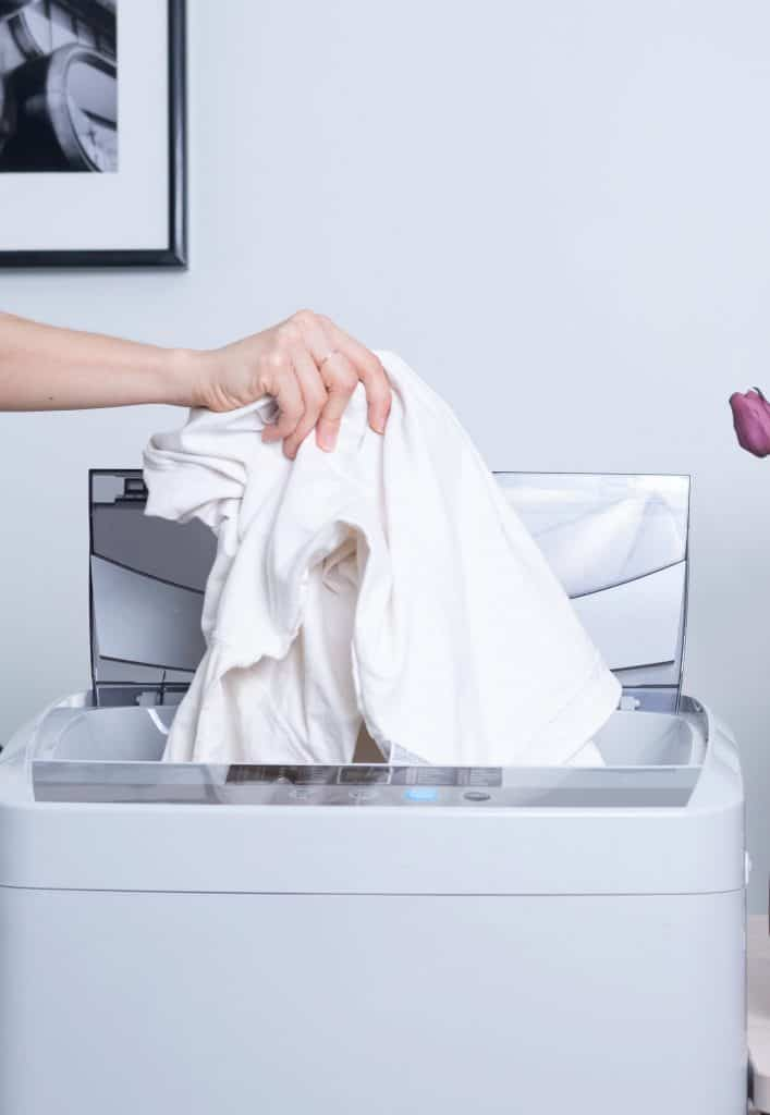 white laundry being placed in a washing machine