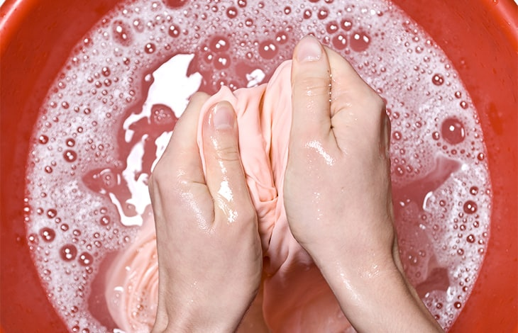 hands scrubbing peach fabric in a red basin filled with soapy water