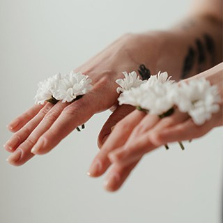 clean, manicured hands with small white flowers between their fingers